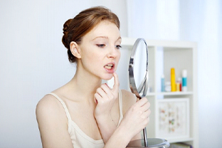 woman looking at her mouth in a mirror