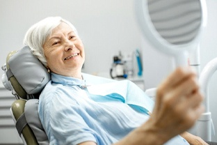 older woman sitting in dental chair and smiling at hand mirror