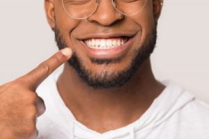 close-up of a man pointing to his smile with dental implants in Peabody