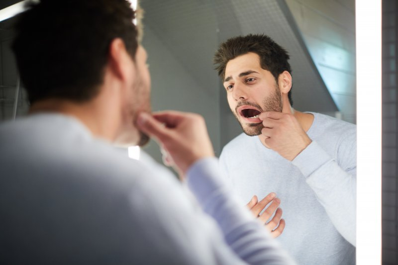 Man trying to place knocked-out tooth back into his mouth